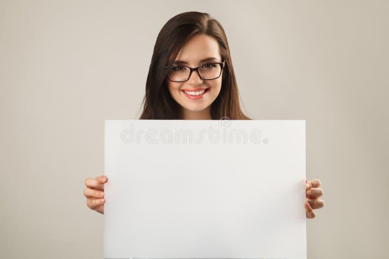 Jeune belle femme en verres tenant le conseil vide blanc images stock