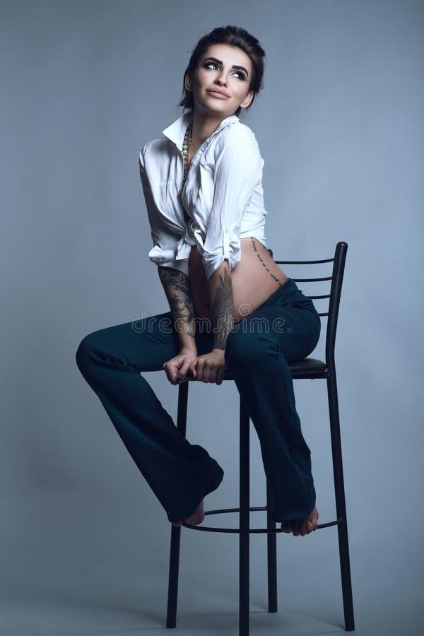 Jeune belle femme enceinte de sourire tatouée élégante avec des cheveux d'updo utilisant le pantalon à la mode de bleu marine du  photographie stock libre de droits