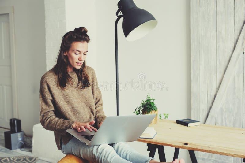 Jeune belle femme faisant des emplettes à la maison en ligne avec l'ordinateur portable et la tasse de café pendant le matin image libre de droits