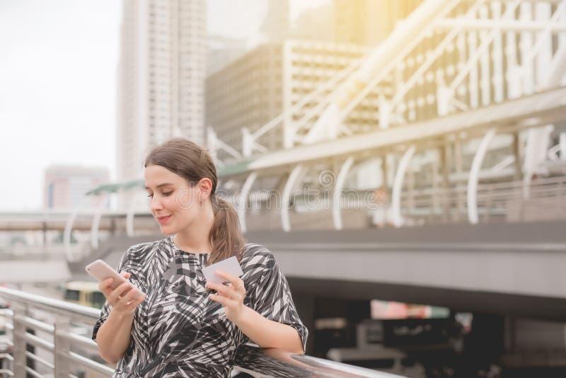 Jeune belle femme faisant des emplettes en ligne avec le téléphone portable à la ville centrale photos libres de droits