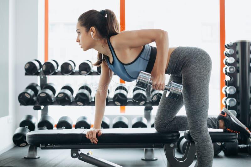 Jeune belle femme faisant des exercices avec l'haltère dans le gymnase photos libres de droits