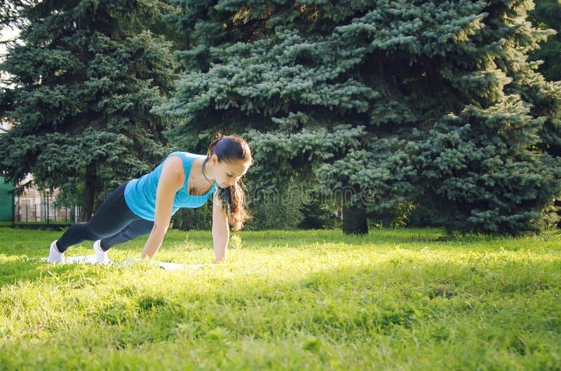 Jeune belle femme faisant des exercices de sport en parc images libres de droits