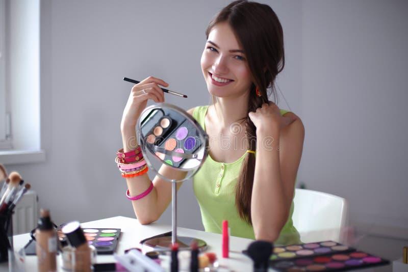 Jeune belle femme faisant le maquillage près du miroir images libres de droits