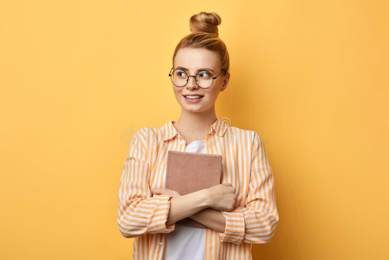 Jeune belle femme heureuse avec le hairbun tenant et tenant le dossier photo stock