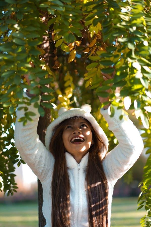 Jeune belle femme heureuse en parc d'automne le jour ensoleillé, jeune femme dans le manteau blanc pendant le coucher du soleil e photo stock