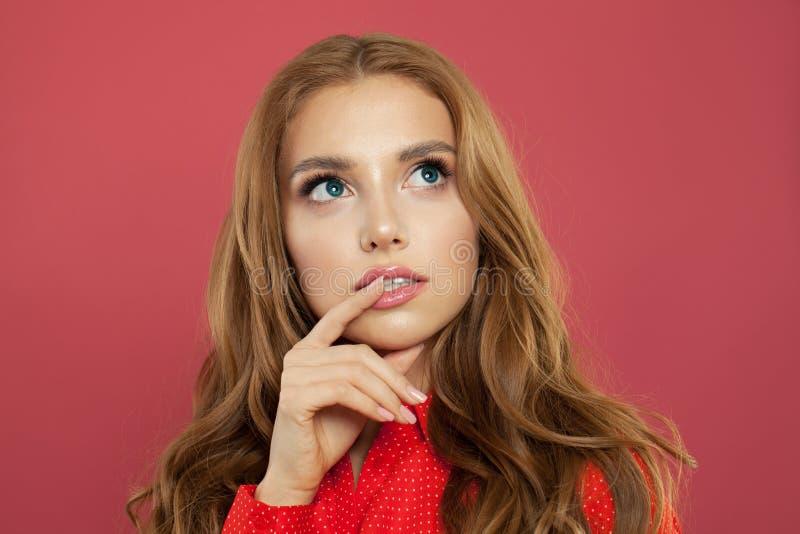 Jeune belle femme imaginant et regardant au-dessus du fond rose photo stock