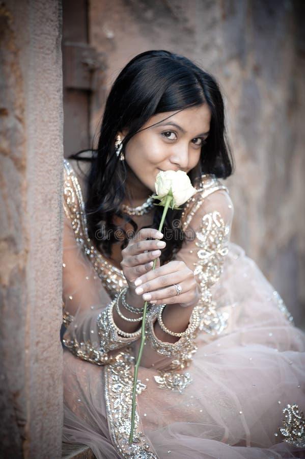Jeune belle femme indienne s'asseyant contre le mur en pierre dehors photos libres de droits