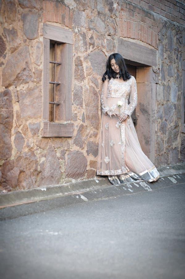 Jeune belle femme indienne se tenant contre le mur en pierre dehors image libre de droits