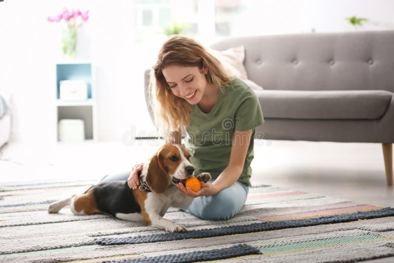 Jeune belle femme jouant avec son chien à la maison photo stock