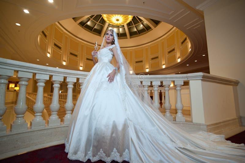 Jeune belle femme luxueuse dans la robe de mariage posant dans l'intérieur luxueux Jeune mariée avec la robe de mariage énorme da image stock