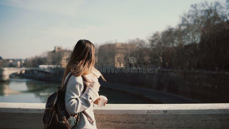 Jeune belle femme marchant le matin ensoleillé sur le pont Le café potable femelle attrayant et ont une balade photo libre de droits