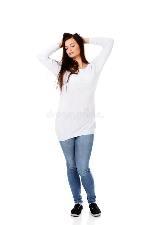Jeune belle femme massant ses propres poils image stock