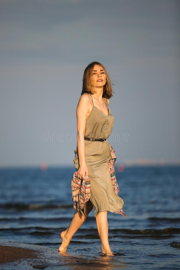 Jeune belle femme mince avec les cheveux légers courts portant la robe verte d'été marchant à la côte au coucher du soleil photo stock