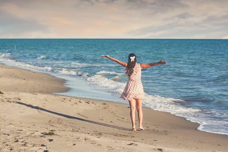 Jeune belle femme mince sur la plage, espiègle, danse, sautant, vacances d'été, ayant l'amusement, humeur positive photos libres de droits