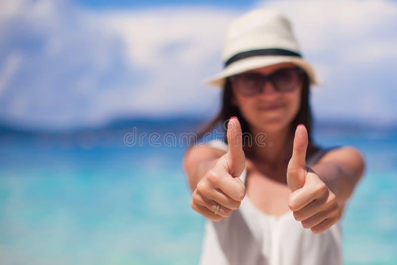 Jeune belle femme montrant des pouces sur photographie stock libre de droits