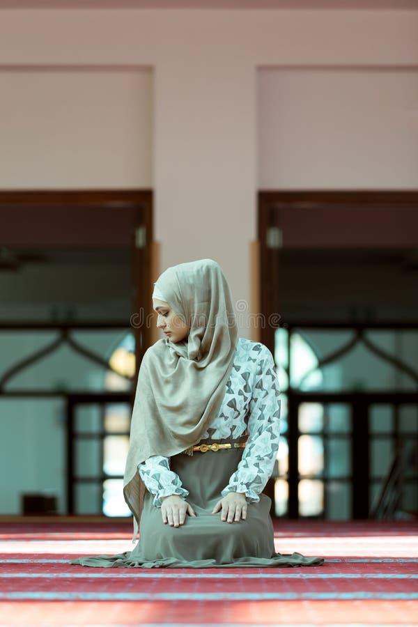 Jeune belle femme musulmane priant dans la mosquée images libres de droits