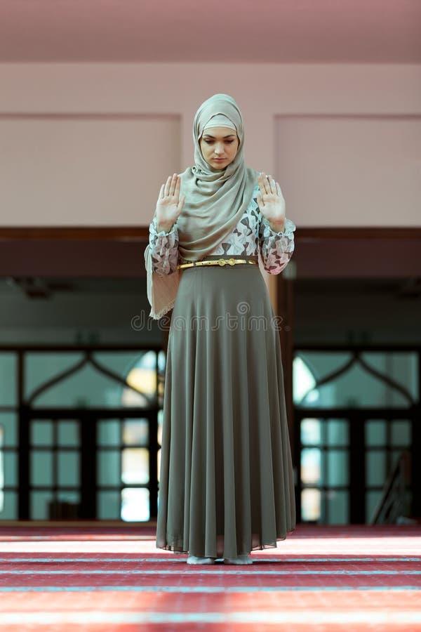 Jeune belle femme musulmane priant dans la mosquée photos stock