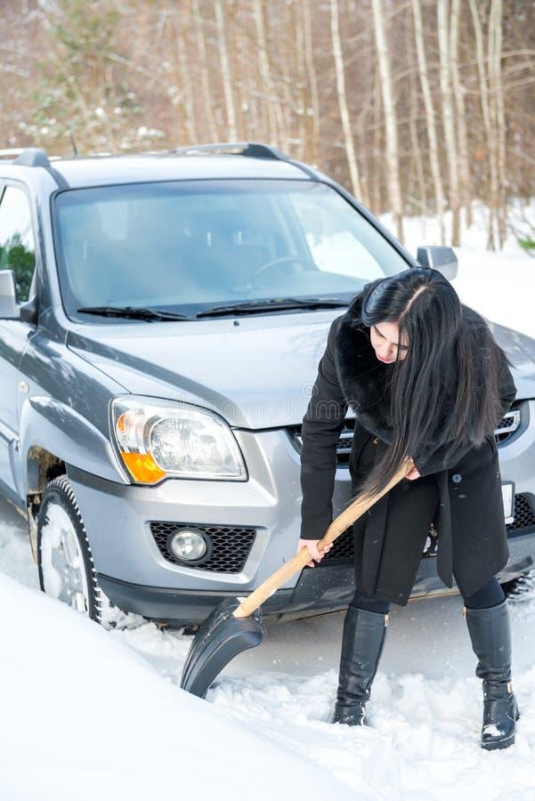 Jeune belle femme pellant et enlevant la neige de sa voiture, images libres de droits