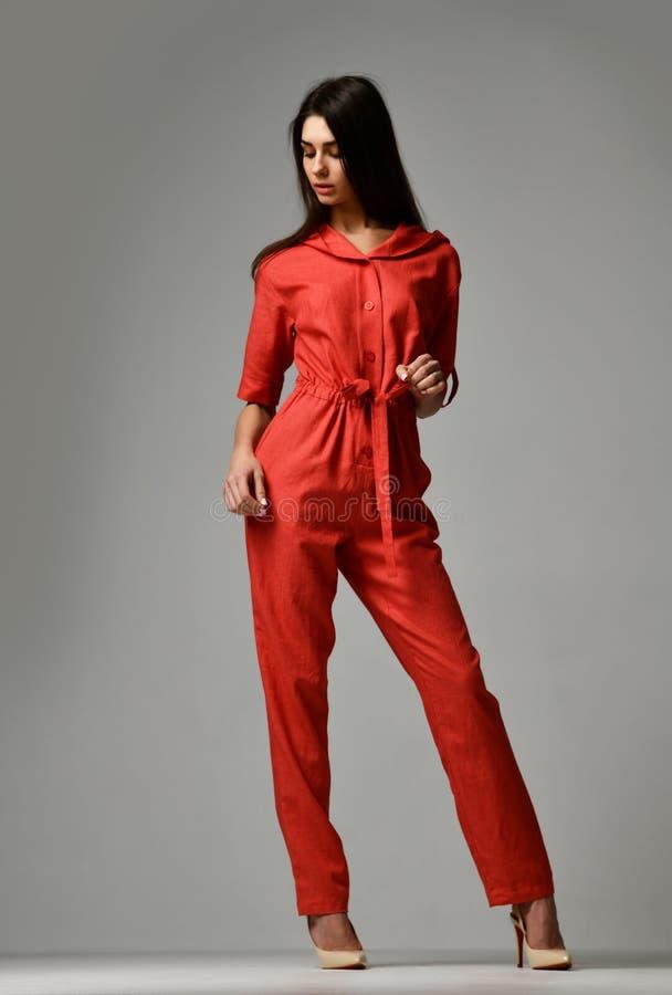 Jeune belle femme posant dans la nouvelle robe rouge de costume de mode avec le pantalon et le capot images stock