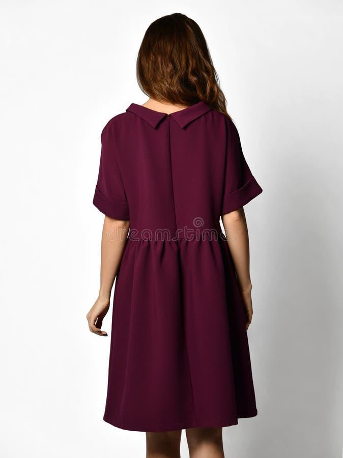 Jeune belle femme posant dans la nouvelle vue arrière pourpre foncée de manteau de robe d'hiver de mode photo libre de droits