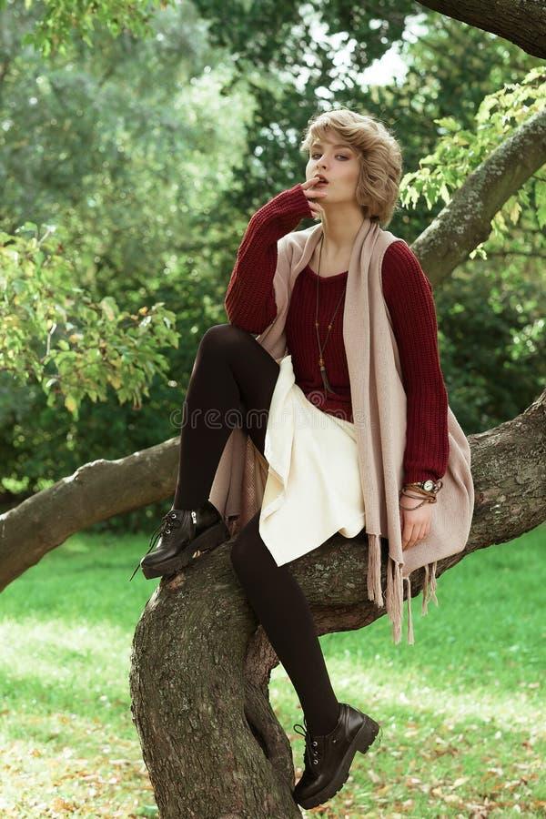Jeune belle femme posant sur un arbre photos stock