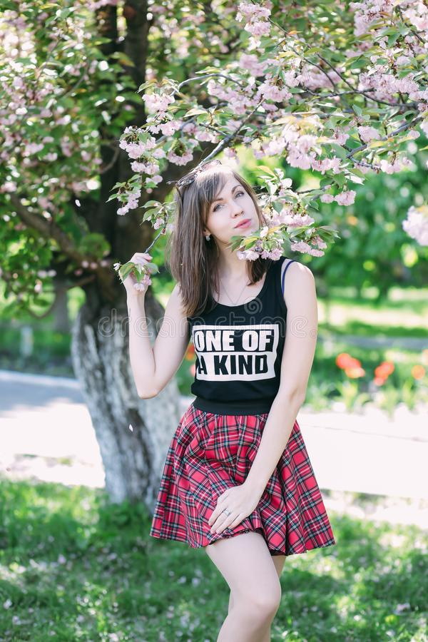 Jeune belle femme près d'arbre de floraison de Sakura Fleurs, ressort et concept roses de la jeunesse Fille élégante images stock