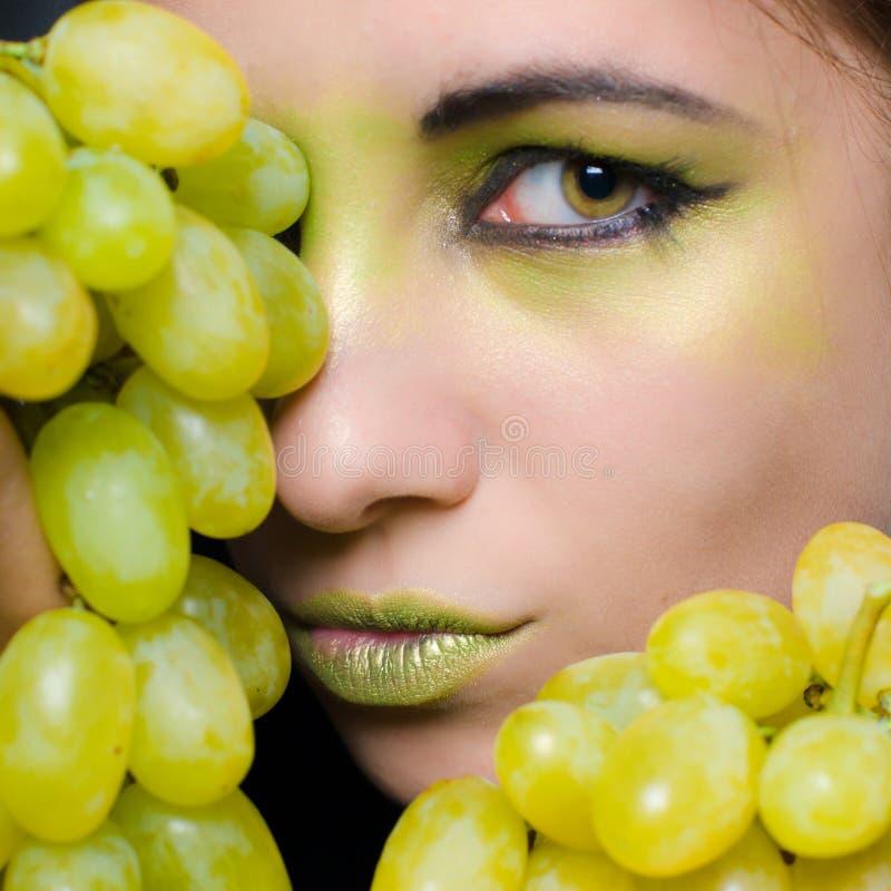 Jeune belle femme retenant le plan rapproché vert de raisins image libre de droits