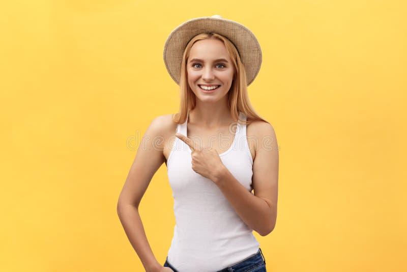 Jeune belle femme riante dans le T-shirt regardant et se dirigeant loin avec le doigt au-dessus du fond jaune image stock