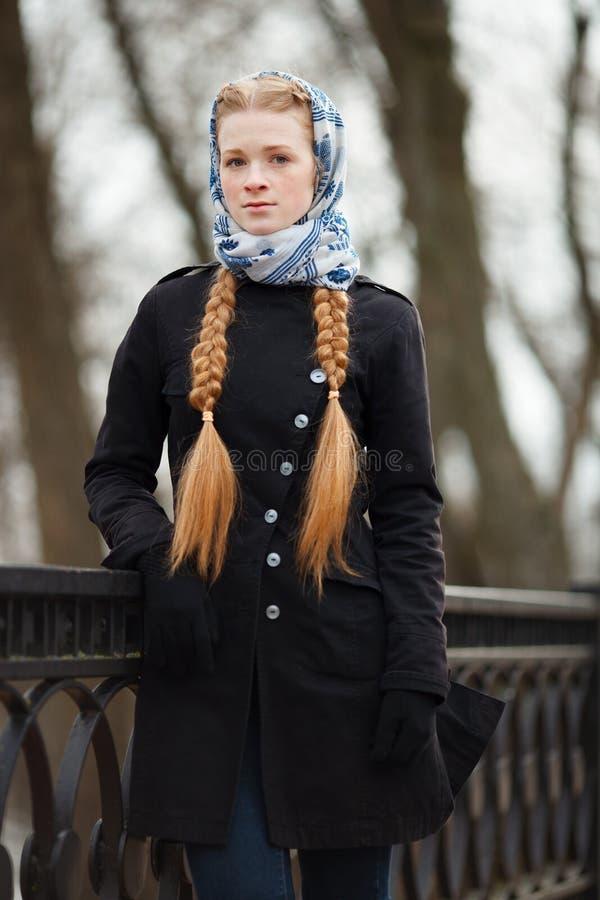 Jeune belle femme rousse à la mode avec la coiffure de tresses dans la veste élégante de fossé de noir de denim de headcraft blan photos libres de droits
