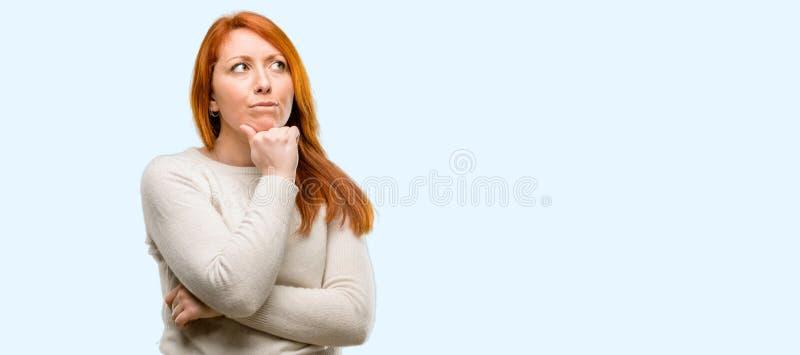 Jeune belle femme rousse au-dessus de fond bleu photo stock