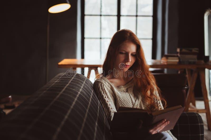 Jeune belle femme rousse détendant à la maison dans le livre confortable de soirée et de lecture d'automne photographie stock libre de droits