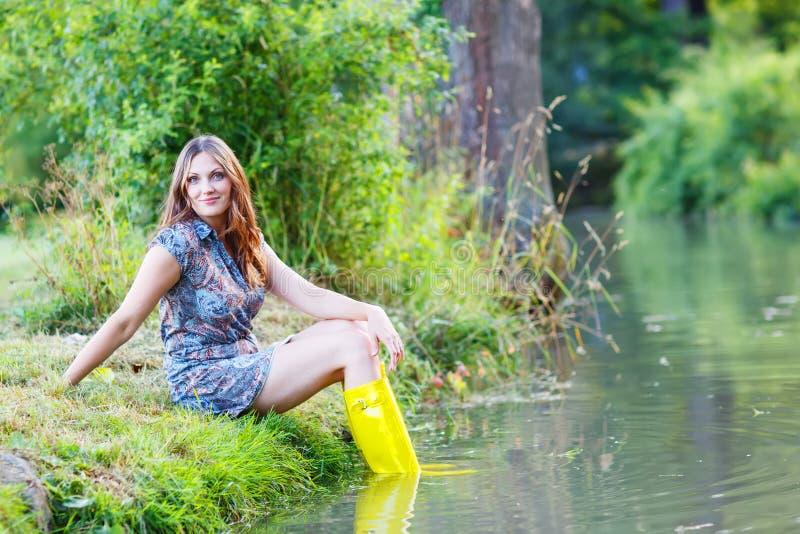 Jeune belle femme s'asseyant dans des canots en caoutchouc jaunes de pluie par un r photo stock