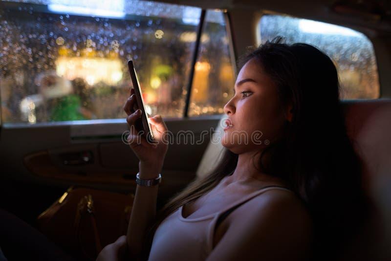 Jeune belle femme s'asseyant dans la voiture de taxi tout en à l'aide du téléphone portable la nuit image stock