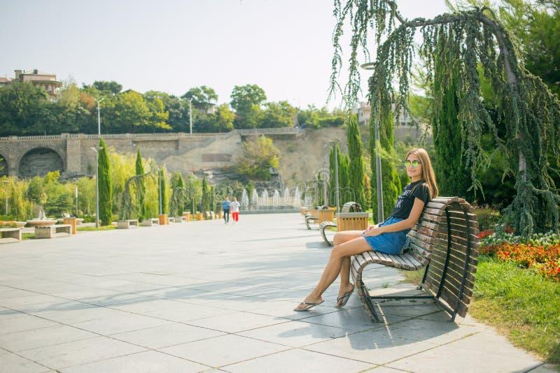 Jeune belle femme s'asseyant sur le banc dans la jolie fille de parc à l'extérieur sur la nature de jour d'été Fille attirante en image libre de droits