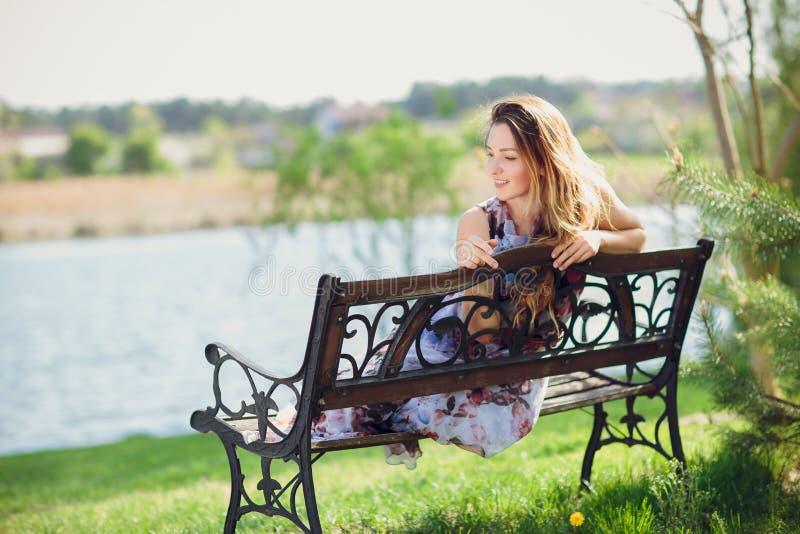 Jeune belle femme s'asseyant sur le banc dans la jolie fille de parc à l'extérieur sur la nature de jour d'été la fille attirante image stock