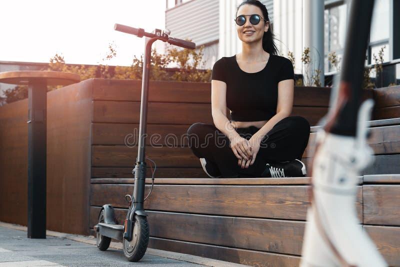 Jeune belle femme s'asseyant sur le banc pr?s du scooter ?lectrique de coup-de-pied photographie stock libre de droits