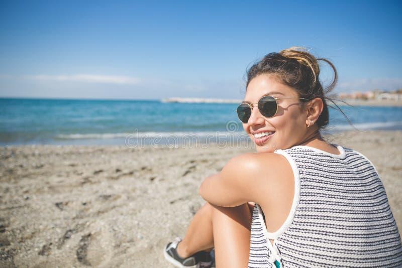 Jeune belle femme s'asseyant sur le sourire de plage photo libre de droits