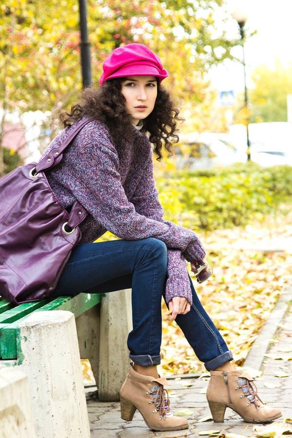 Jeune belle femme s'asseyant sur un banc en parc de ville photo libre de droits