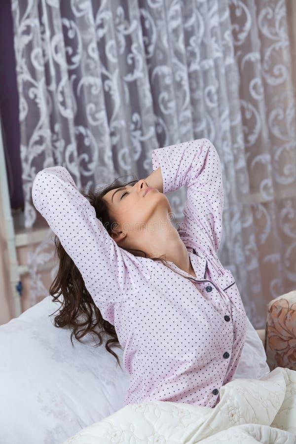 Jeune belle femme se réveillant dans la chambre légère Femme décontractée se situant dans le lit dans les vêtements de nuit photos libres de droits