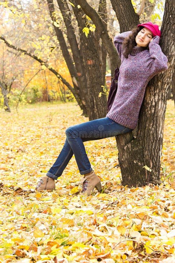 Jeune belle femme se reposant en parc de ville d'automne photographie stock