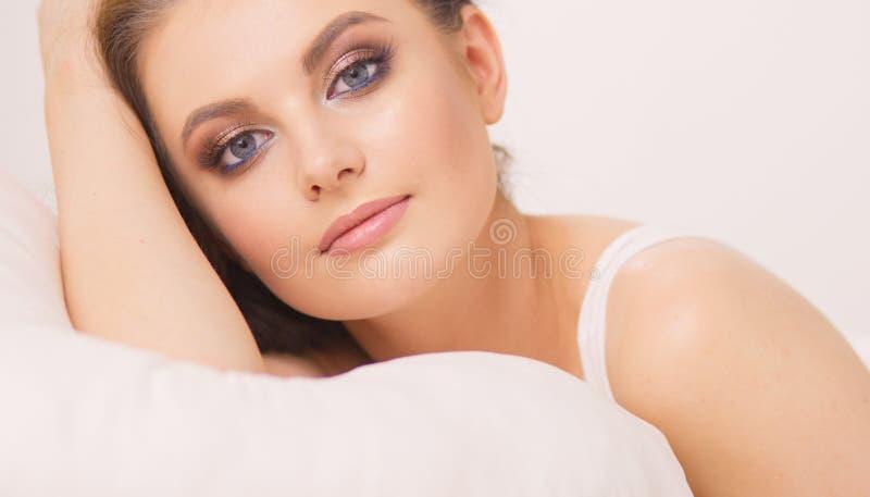 Jeune belle femme se situant dans le lit photo stock