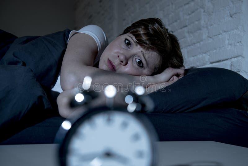 Jeune belle femme se situant dans le lit tard la nuit souffrant de l'insomnie essayant de dormir photos stock