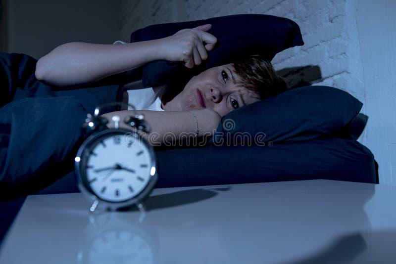 Jeune belle femme se situant dans le lit tard la nuit souffrant de l'insomnie essayant de dormir photo libre de droits