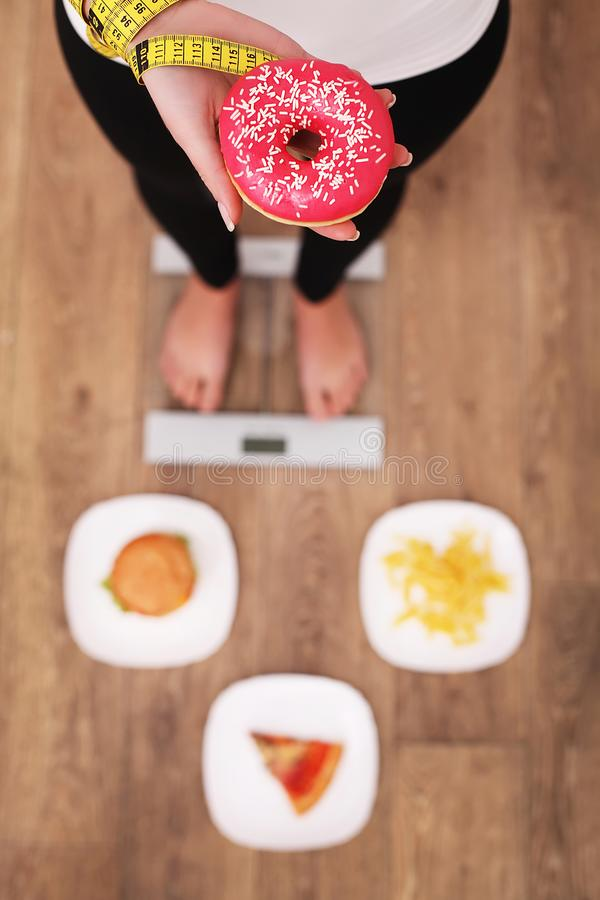 Jeune belle femme se tenant sur des échelles et tenant un beignet Le concept de la consommation saine Style de vie sain Régime images stock