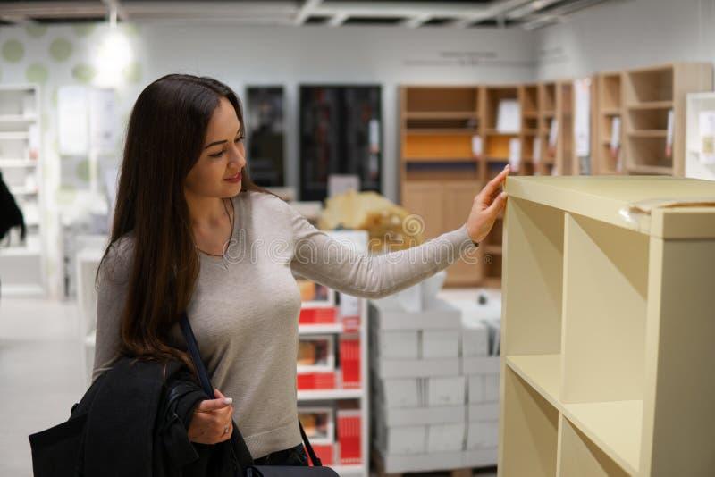 Jeune belle femme se trouvant nouveaux meubles, décoration image libre de droits
