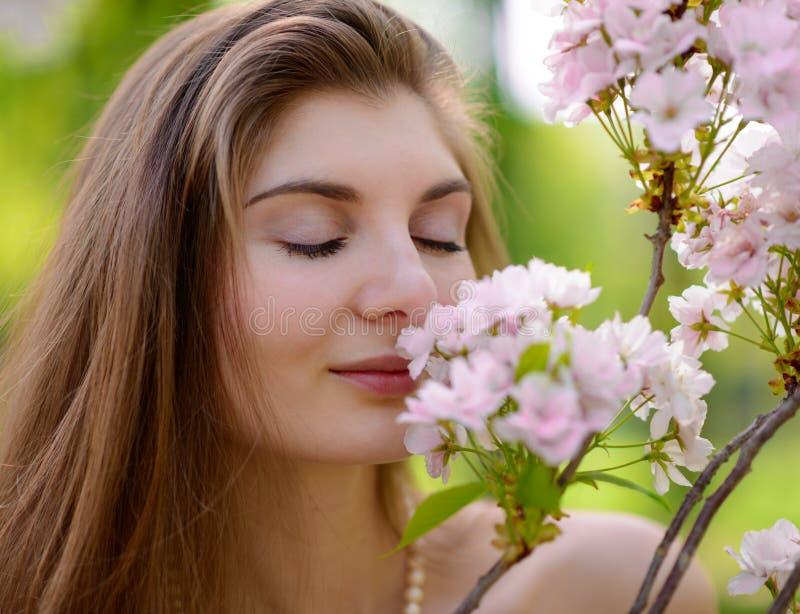 Jeune belle femme sentant Sakura Flowers rose photo stock
