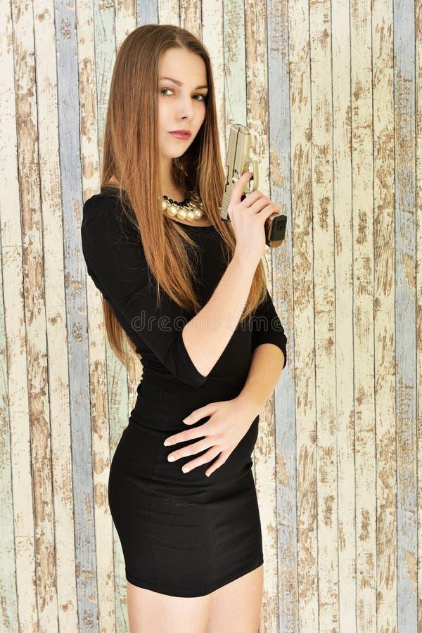 Jeune belle femme sexy jugeant le pistolet disponible photo libre de droits