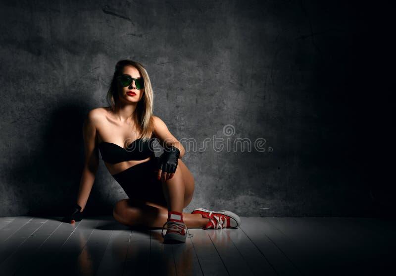 Jeune belle femme sexy sensuelle posant dans la veste en cuir noire de mode sur le mur foncé images libres de droits
