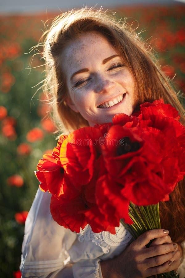 Jeune belle femme souriant dans un domaine de pavot images stock