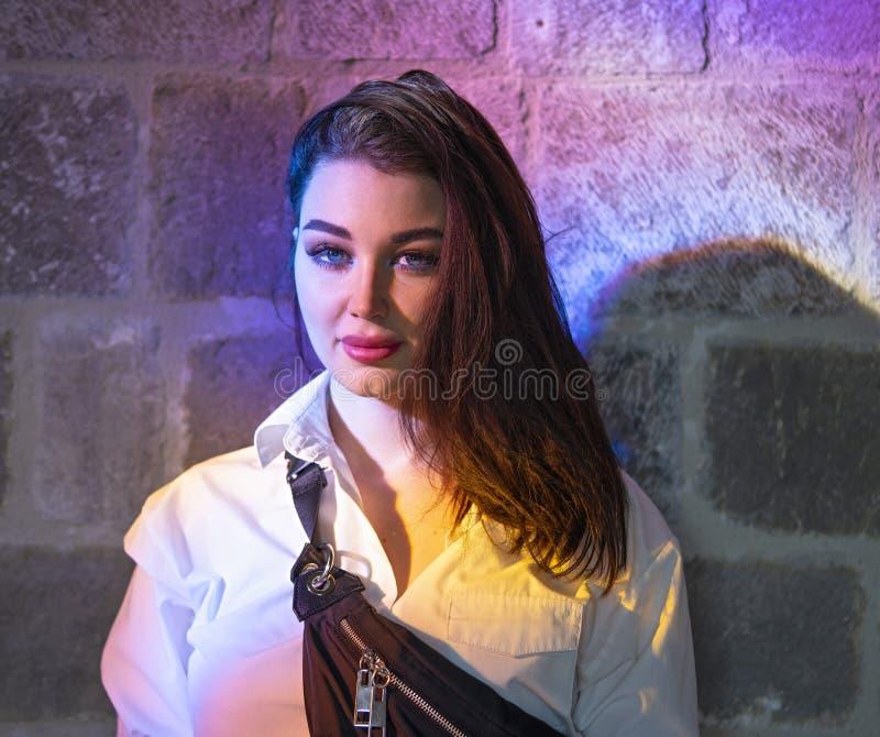 Jeune belle femme sous la lumière multicolore lumineuse dans l'église antique photographie stock libre de droits